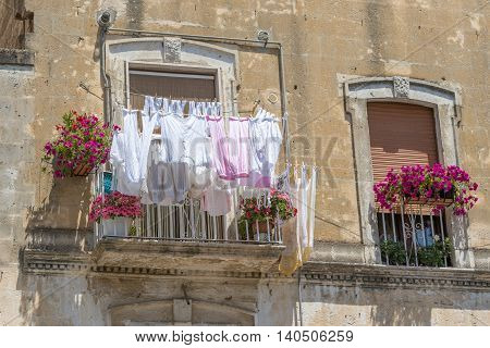 Typical Italian balcony in an old house with drying laundry and pots of blooming flowers