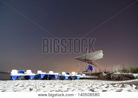 glider is on the night beach loungers and sea among the stars
