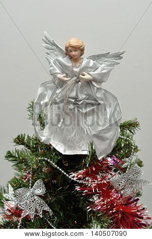 An angel tree topper on top of a Christmas tree