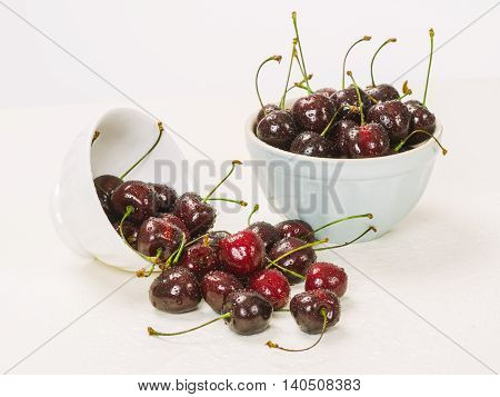 Photo of two bowls of wet cherries over white background.