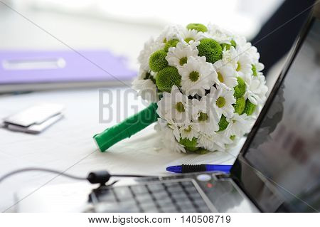 Wedding bouquet of white flowers on a table next to a laptop.