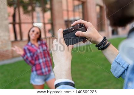 Young male photographer is taking shots of young woman. Girl is standing and smiling. Focus on retro camera