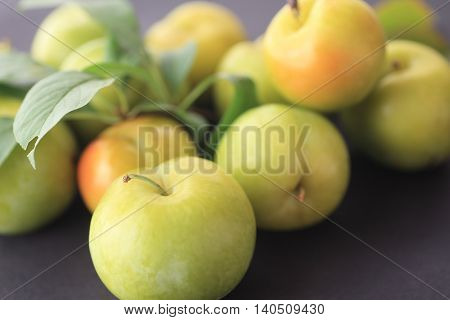 Fresh ripe summer fruits with leaves on a dark background