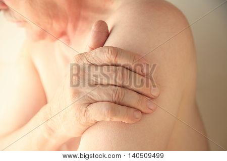 An older man with his hand on an area of soreness on his upper arm
