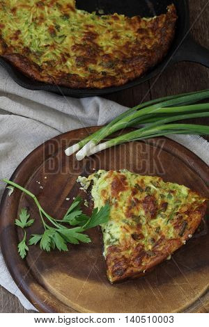 a piece of casserole of zucchini with herbs on a wooden table