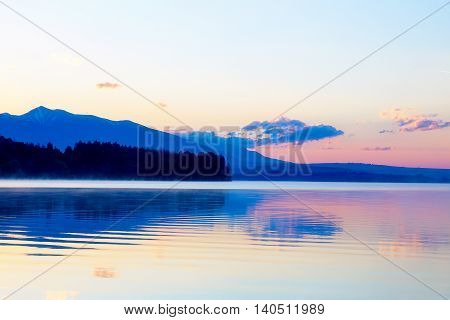 beautiful landscape with mountains and lake at dawn in golden, blue and purple tones