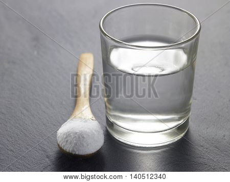 baking soda with glass of water on the black background