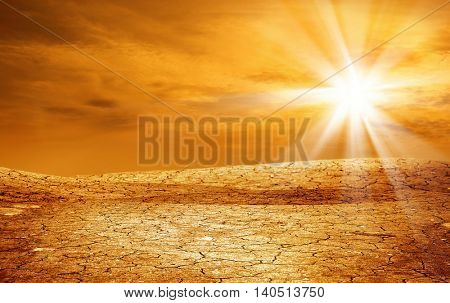 landscape shot of dried and cracked land over sunset.
