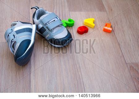 children's shoes for fall and toys on wooden background with place for text. first shoes baby how to choose the size. a child's soul. clothing.