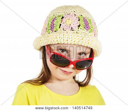 Cute fashion little girl looks out from under sunglasses on a white background.