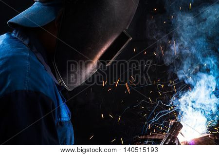 A worker in blue overalls and a baseball cap and a mask is welding metal construction in a cloud of smoke and sparks