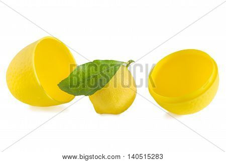 Lemon with green leaf and open yellow plastic storage container in shape of lemon isolated over white. Horizontal.
