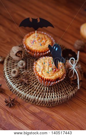 Halloween orange sprinkled cupcakes with pumpkin cheese cream and scary ghost and bat decorations