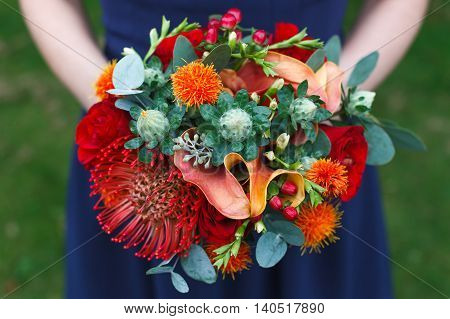 Colorful bouquet of roses, carthamus, nutans and hypericum berries
