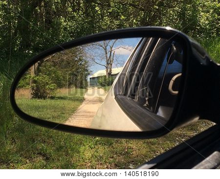 Dirt path to barn in beautiful scenery, viewed through rear view mirror
