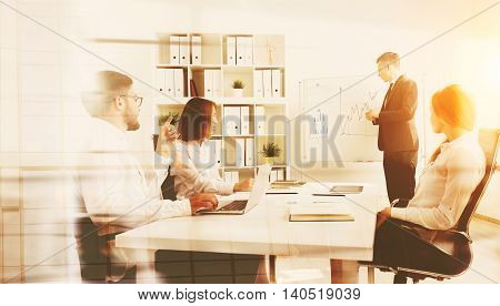 Businessman explaining graphs to his coworkers sitting at table and taking notes. One of them is using laptop another notebook. Tablet on floor. Concept of teamwork. Toned image. Double exposure