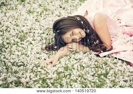 Little Girl On Green Grass With Petals