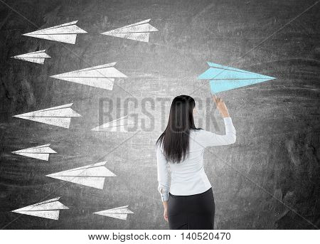 Woman in business suit drawing paper plane on chalkboard. All other aircrafts are flying in different direction. Concept of new and original way to solve challenging problem in business.