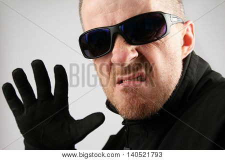 the man in dark glasses with an angry expression