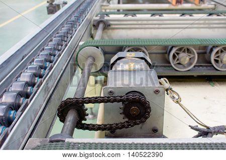 Motor chain drive shaft in conveyor line.