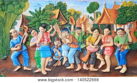 Stone carving and painting of traditional Thai musical instrument and Thai dance on temple wall