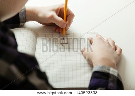 Unidentifiable Boy Writing Backwards In Notebook