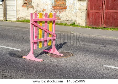 Bright temporary wooden barrier pits on road