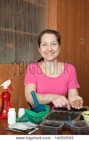 Mature Woman Sows Seedlings