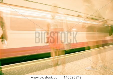 Transport background abstract blurred images of waiting on platform commuters and train moving in station typically modern urban life.