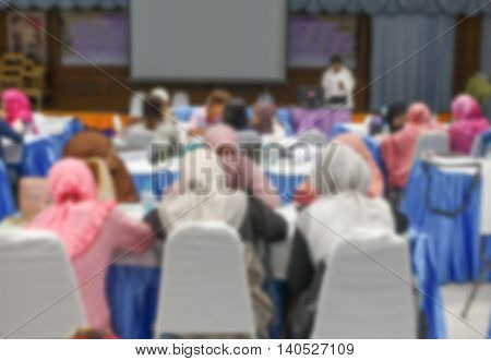 Blur blurred  abstract of university students sitting in a lecture room with Movie screen  education high school, technology and people concept