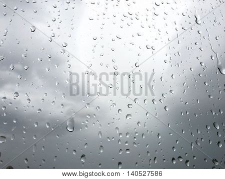 raindrops on glass window grey sky background