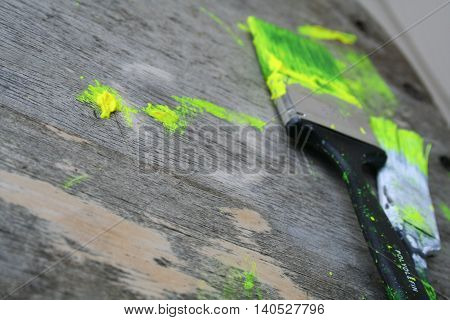 Neon green paint brushes and paint spots on a table