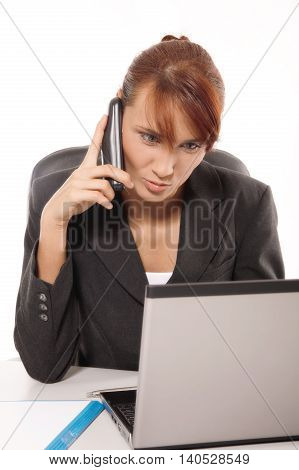 Business concept - Blonde businesswoman talking on the phone while working on computer at the office