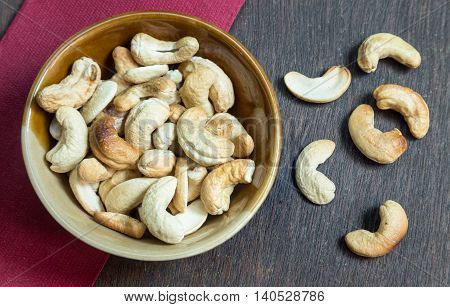 Bowl of cashew nuts from above. On wood background.