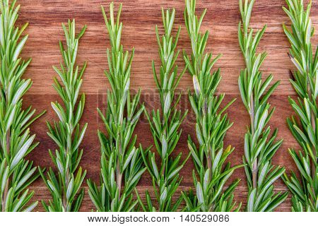 Sprigs of rosemary lined up vertically on a wood cutting board