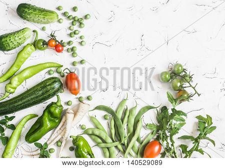 Fresh vegetables - zucchini cucumbers green peas and beans parsnips peppers tomatoes onions on a white background. Concept of a healthy diet food