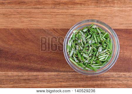 Chopped rosemary in a glass bowl, on a wood cutting board