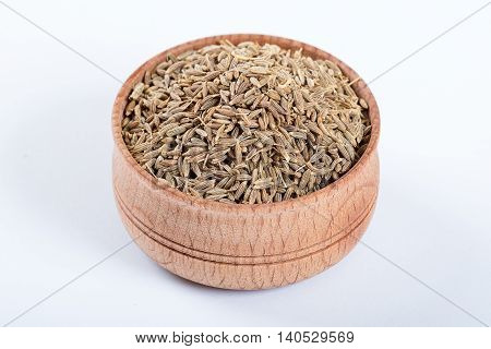 Cumin seeds or caraway in a wooden bowl isolated on white background