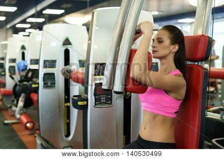 At gym. Beautiful young woman exercising on simulator