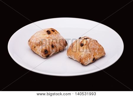 Two sandwich buns with raisons on white plate