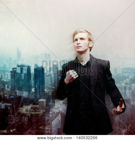 ambitious young man on a background of megalopolis, double exposure