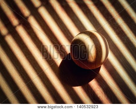 abstract background wooden ball covered with the shadow of sunblinds