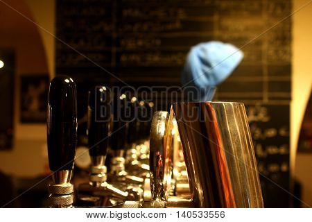 A close view of golden beer taps with black handles and a blue cap at the background