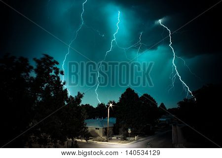 Abstract lightning strikes with a house and a highlighted lamp in the foreground