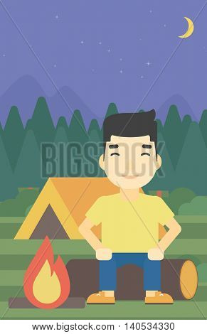 An asian travelling man sitting on a log near a fire on a background of camping site with tent. Man sitting near a campfire at a campsite. Vector flat design illustration. Vertical layout.