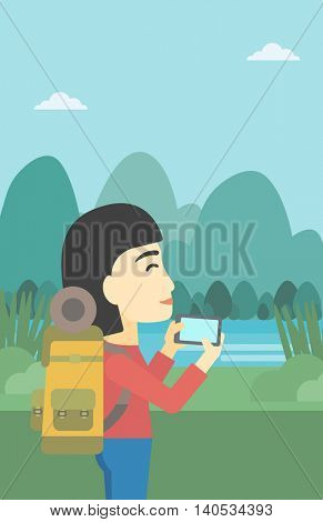 An asian woman taking photo of landscape with mountains. Young hiking woman with backpack taking photo with her cellphone. Vector flat design illustration. Vertical layout.
