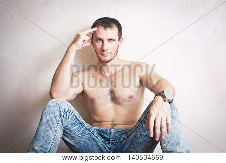 Portrait of young attractive man sitting on the floor near the wall