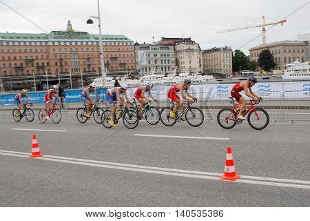 STOCKHOLM SWEDEN - JUL 02 2016: Group of colorful male triathlete cyclists on a bridge in the Men's ITU World Triathlon series event July 02 2016 in Stockholm Sweden