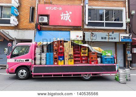 TOKYO JAPAN - 18 JULY 2016 - Pink beverage delivery truck parks on a street in Shinjuku Tokyo Japan on July 18 2016.