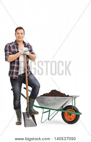Full length portrait of a young gardener posing with a shovel by a wheelbarrow with dirt isolated on white background